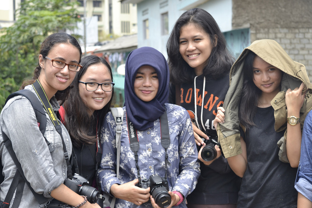 Young undergrads on a first photoshoot.  Cynthia (in Hijab) wears jeans and boy's sneakers; Lisa, from North Sumatra (the tall girl to Cynthia's left) is a Christian.  They're all eager to become journalists and write about Indonesia's future.